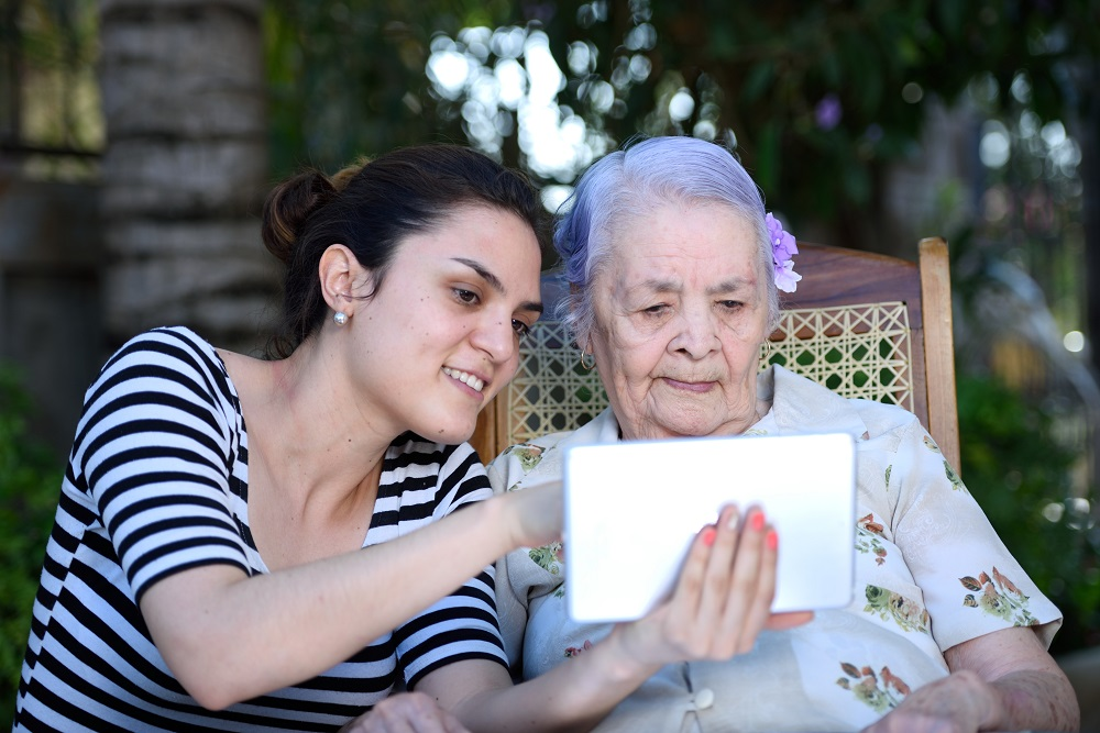 girl show how to work tablet to grandma