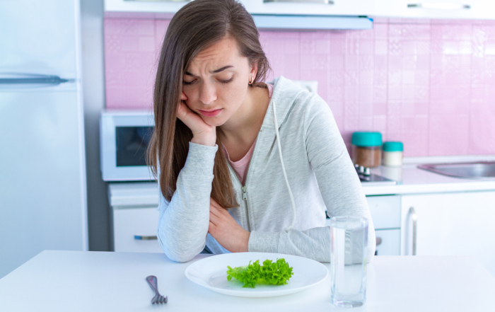 Sad unhappy young woman is tired of dieting and not wanting to e