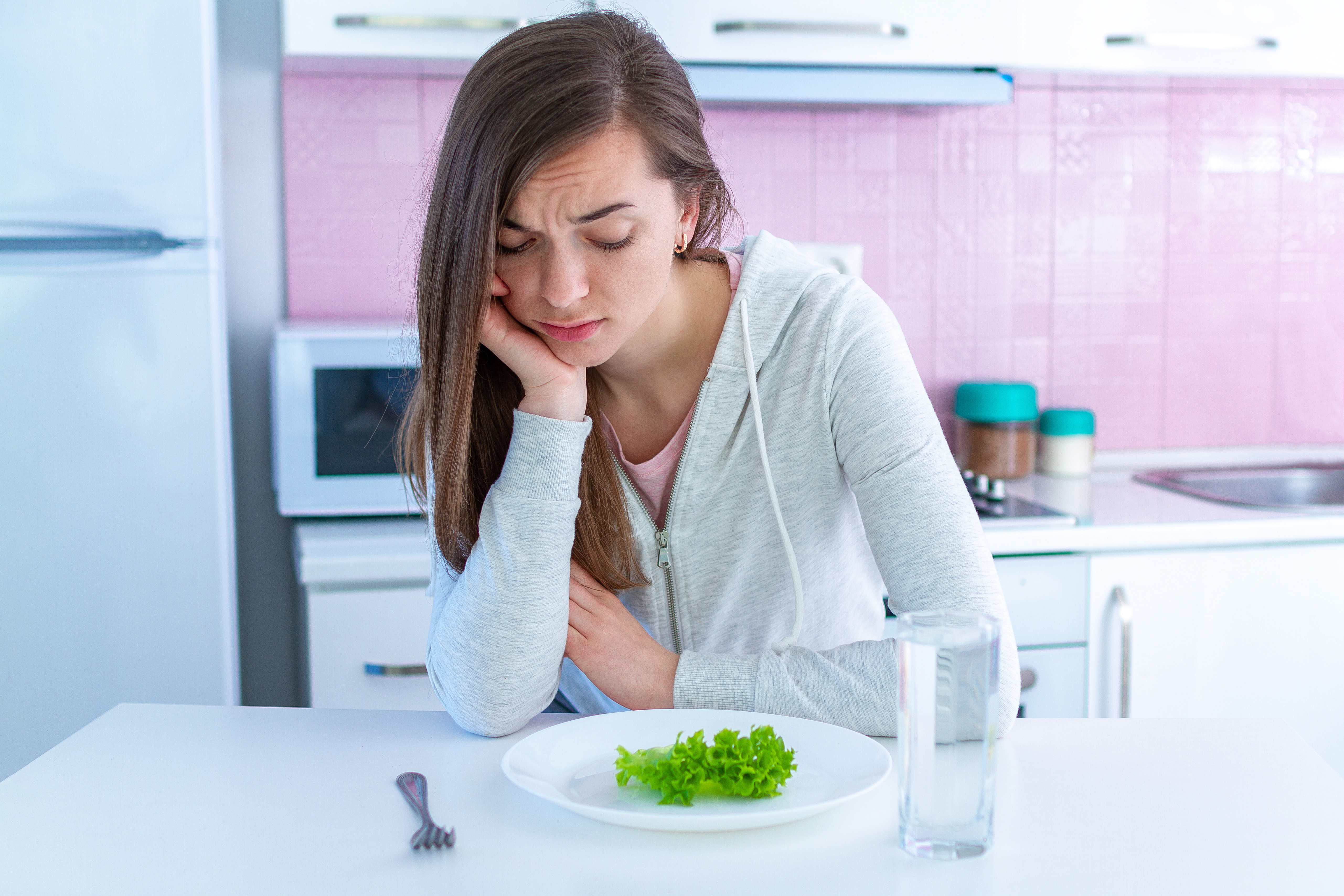 Sad unhappy young woman is tired of dieting and not wanting to eat organic, clean healthy food